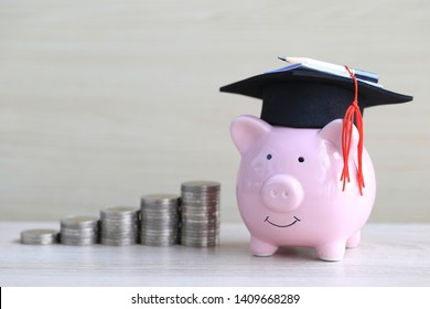 Graduation hat on pink piggy bank with stack of coins money on wooden background, Saving money for education concept