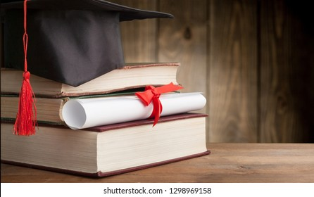 Graduation hat and stacks of books