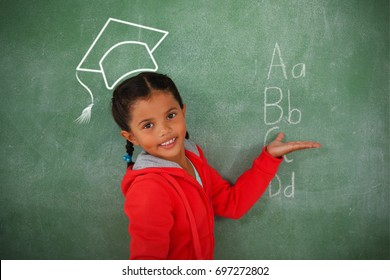 Graduation hat vector against young girl gesturing over chalk board