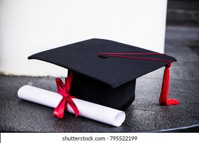 Graduation mortarboard and diploma  tied with red ribbon.  Education concept Copy Space.