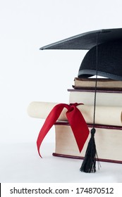 A graduation mortarboard on top of a stack of books, with parchment scroll tied in red ribbon.
