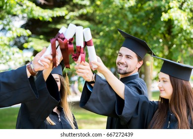 Graduation Student Commencement University Degree Concept - group of happy international students in mortar boards and bachelor gowns with diplomas