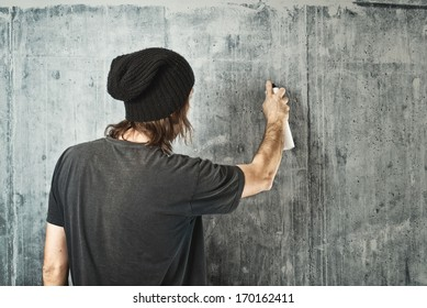 Graffiti artist in black clothes spraying the wall/
