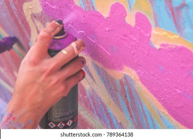 Graffiti artist Hand painting with aerosol spray on the wall, asphalt paint work. Urban man performing with murales - Concept of colourful  modern art - Focus on his hand .graffiti, wall, paint, art,