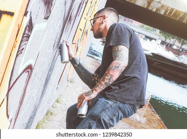 Graffiti artist painting with a color spray can on the wall in the city - Young guy doing a mural next to the river -  Urban and street art lifestyle concept