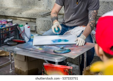 Graffiti artist painting on the white paper at the street