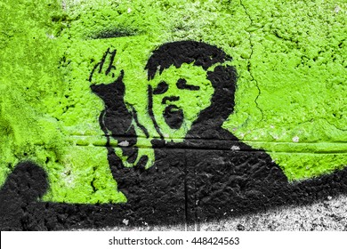 Graffiti on the wall, angry kid on a green background. fuck you