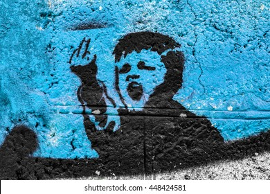 Graffiti on the wall, angry kid on a blue background. fuck you
