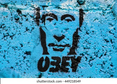 Graffiti on the wall, obey Putin on a blue background