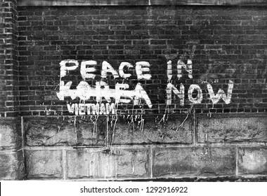 Graffiti, peace now. Korea, Vietnam. Brick wall.