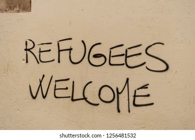 """Graffiti with the political slogan """"Refugees Welcome"""" on a wall in Venice in 2018."""