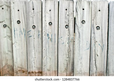 A graffiti slogan on wooden planks stating have a nice day