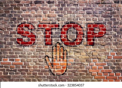 Graffiti stop letters with hand palm on  brick wall.