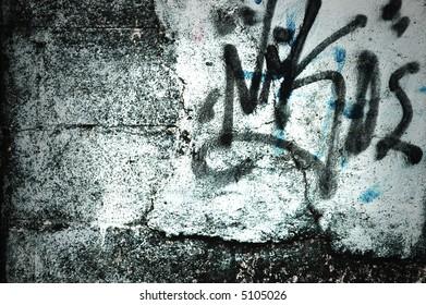 graffiti tags on grungy wall at night.