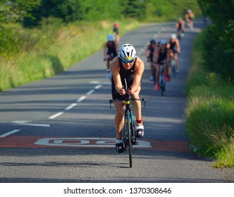 GRAFHAM, CAMBRIDGESHIRE, ENGLAND - AUGUST 06, 2017:  Female Triathlete on road cycling stage of triathlon.
