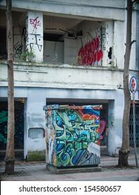 Grafitti on power box next to abandoned house