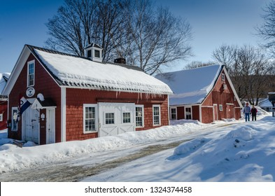 Grafton, NY / USA - 03-06-2015: Couple taking a winter stroll past historic blacksmith shop in rural Vermont.