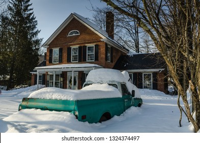 Grafton, NY / USA - 03-06-2015: Green pickup truck covered in snow in front of red brick colonial house.