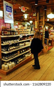 Grafton, VT, USA December 17, 2009 An adult woman browses the varieties of maple syrup for sale at the Vermont Country Store in Grafton, Vermont