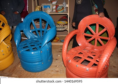 Grahamstown Makhanda, Eastern Cape, South Africa - July, 2nd, 2019: Creative chairs made out of car tires, painted in bright primary colours at an outdoor stall at the National Arts Festival.