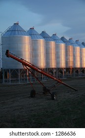 grain auger with bins at sunset