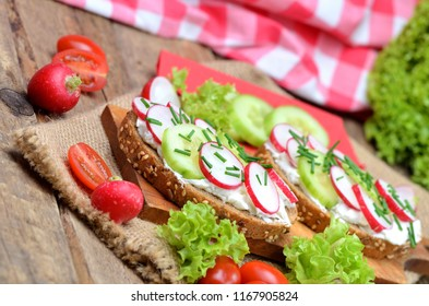 Grain bread with curd cheese, fresh radish, cucumber and tomatoes on a wooden cutting board - concept of healthy fitness breakfast or snack