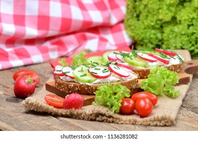 Grain bread with spread, fresh radish, cucumber and tomatoes on - concept of healthy fitness breakfast or snack, fresh salad in the background