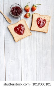 Grain bread topping with red heart shaped homemade strawberry jam and decorated with strawberries fruits on white wooden table. Romantic breakfast in Valentines Day. Concept about love and wedding.