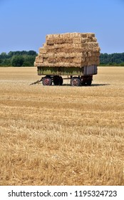Grain field just threshed. Straw bales on a trailer in a field of North Rhine-Westphalia, Germany