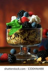Grain free oat free paleo diet granola breakfast served with fresh seasonal berries, coconut milk, and coconut yoghurt.