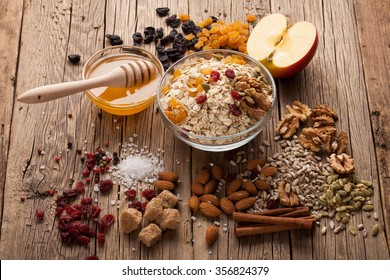 Grain free oat free paleo granola: mixed nuts, seeds, raisins, honey and coconut oil, wooden background, selective focus