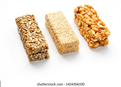 Grain granola bar with peanuts, sesame and seeds in a row on a white background. Top view Three assorted bars, isolate