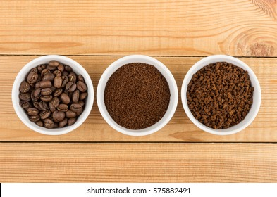 Grain, ground and instant coffee in glass bowls on wooden table. Top view
