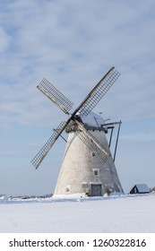 Grain mill on the winter landscape. Dutch windmill and natural background pattern