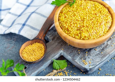 Grain mustard in a bowl and mustard granules in a wooden spoon on a dark textured table, selective focus.