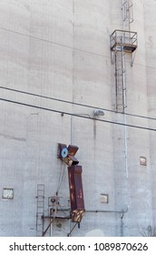grain silo chute and ladder with platform isolated against gray concrete wall of building