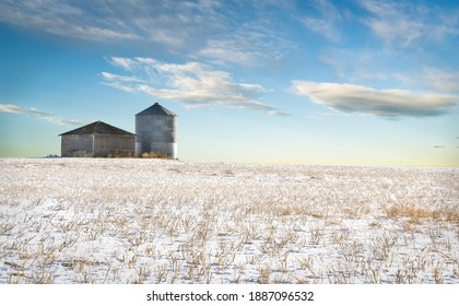 A grain silo next to an old shed sit on a harvested snow covered field on the Canadian prairies in Rocky View County Alberta.