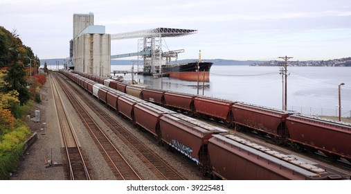 Grain from silos being loaded onto cargo ship on conveyor belt with freight train in foreground