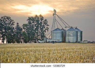 Grain silos and cropped wheat field under a cloudy sunset