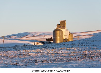 Grain silos on snow covered rolling hills of the Palouse region of Washington, USA