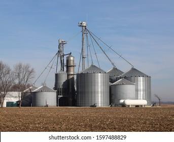 Grain storage bins with a grain drier in a field.