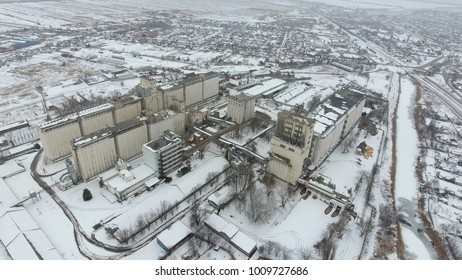 Grain terminal in the winter season. Snow-covered grain elevator in rural areas. A building for drying and storing grain
