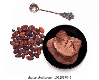 Grains of cocoa and chocolate ice cream vintage spoon on a white background.