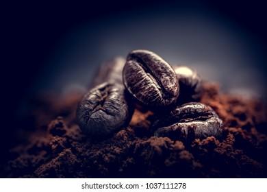 Grains of coffee lie on ground coffee. Unusual photo low key.