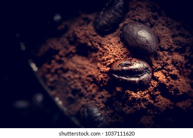 Grains of coffee lie on ground coffee. Unusual photo low key.