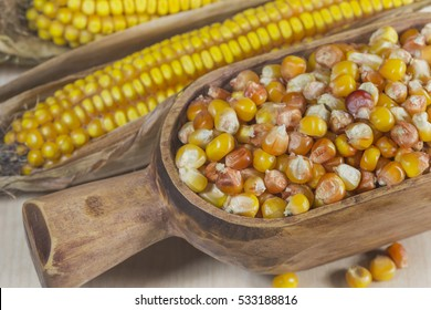 Grains of corn in a wooden bowl and corn on the cob