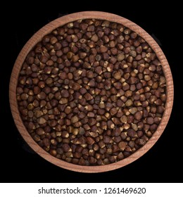 Grains of paradise  in wooden cup isolated on black background. top view