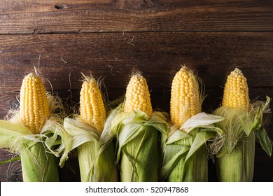 Grains of ripe corn on wooden background.