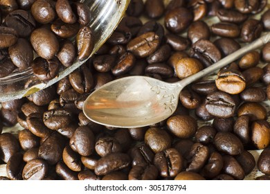 Grains of roasted Arabica coffee with a metal spoon on a background of wooden planks, natural light.