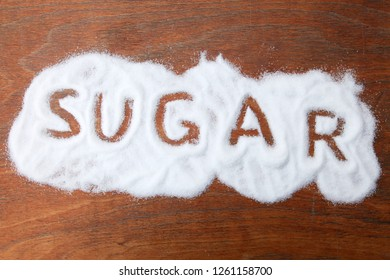 Grains of sugar on the table with the word'sugar'